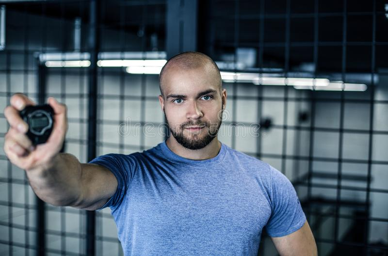 严肃的体育教练的画象有一个秃头的 在健身房的照相机显示一块秒表 锻炼是成功的 ??  库存照片