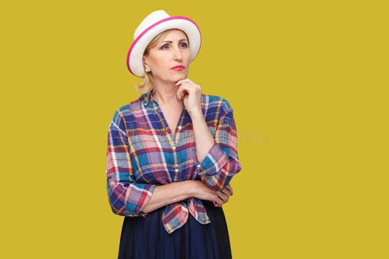 严肃的体贴的现代时髦的成熟妇女画象便装样式的与白色帽子身分,接触她的下巴,询问和 免版税图库摄影