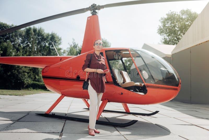 严肃的俏丽的妇女等待的飞行员 免版税库存照片