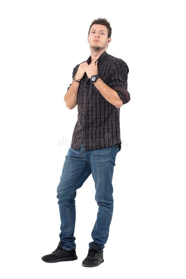 严肃的偶然拉扯衣领的人佩带的牛仔裤和被检查的灰色衬衣 库存照片