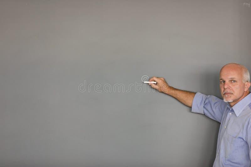 严肃的前辈教或有黑板的讲师 免版税图库摄影