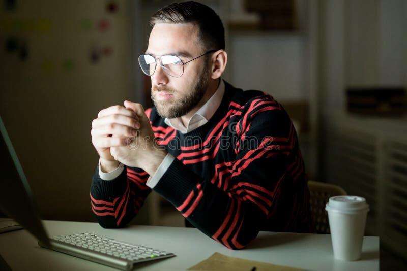 严肃的办工室职员与计算机一起使用在黑暗的办公室 库存图片