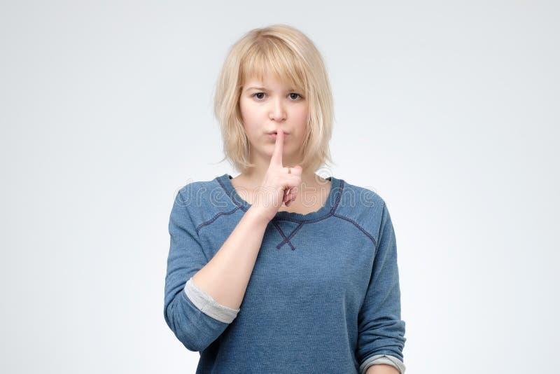 严肃的可爱的女性在蓝色pulover要求保留秘密信息机要,穿戴 图库摄影