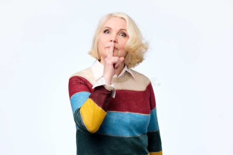 严肃的可爱的白肤金发的妇女要求保持秘密信息机要 免版税库存图片