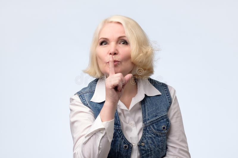 严肃的可爱的白肤金发的妇女要求保持秘密信息机要 免版税库存照片