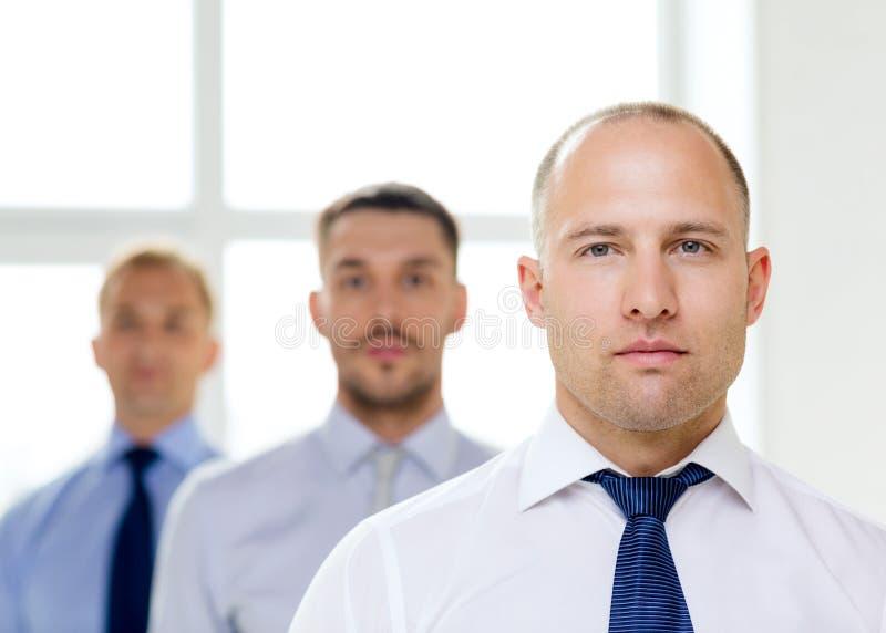 严肃的商人在有队后面的办公室 库存照片