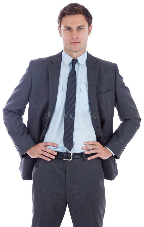 严肃的商人用在臀部的手 免版税库存照片
