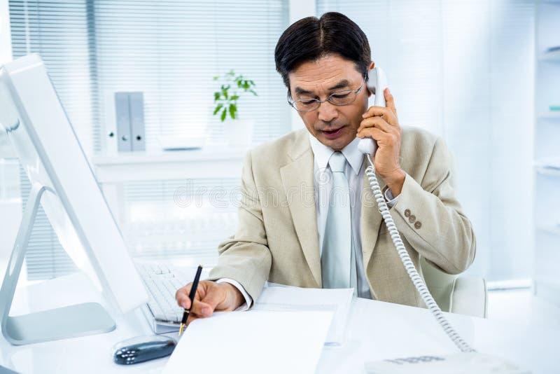严肃的商人谈话在电话 库存图片