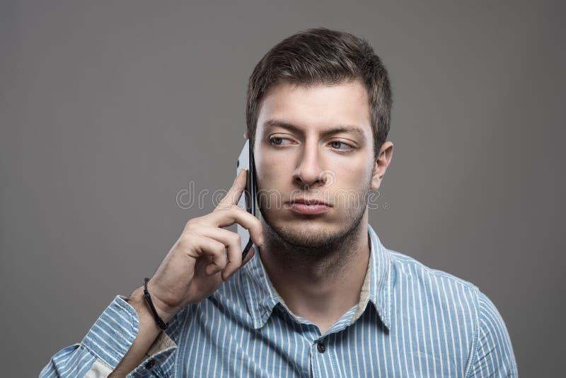 年轻严肃的商人谈话在看的手机  免版税图库摄影