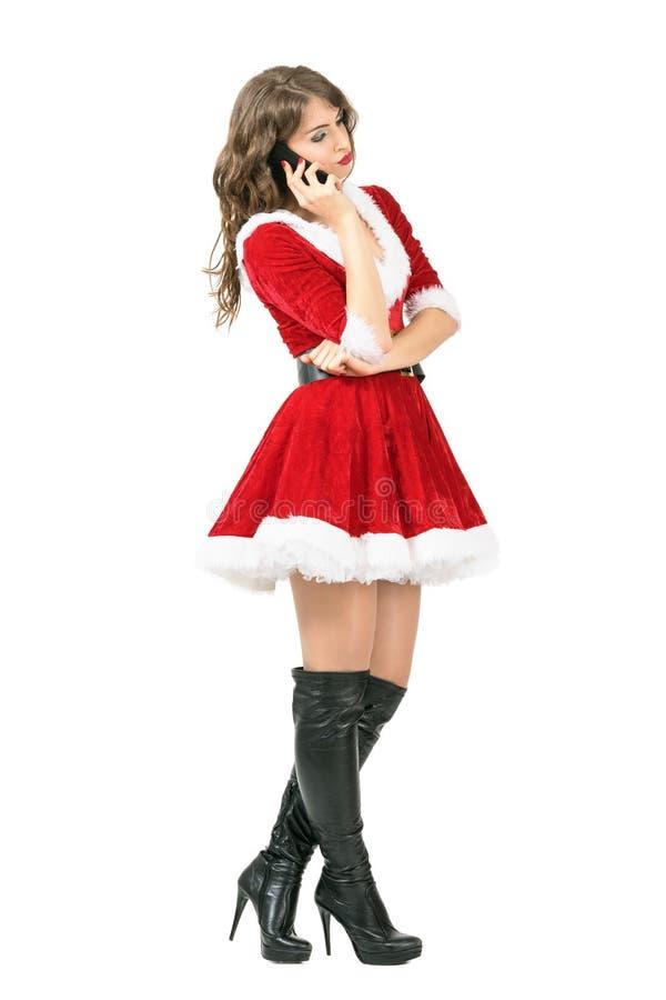严肃的圣诞老人妇女侧视图谈话在看的电话下来 免版税库存图片
