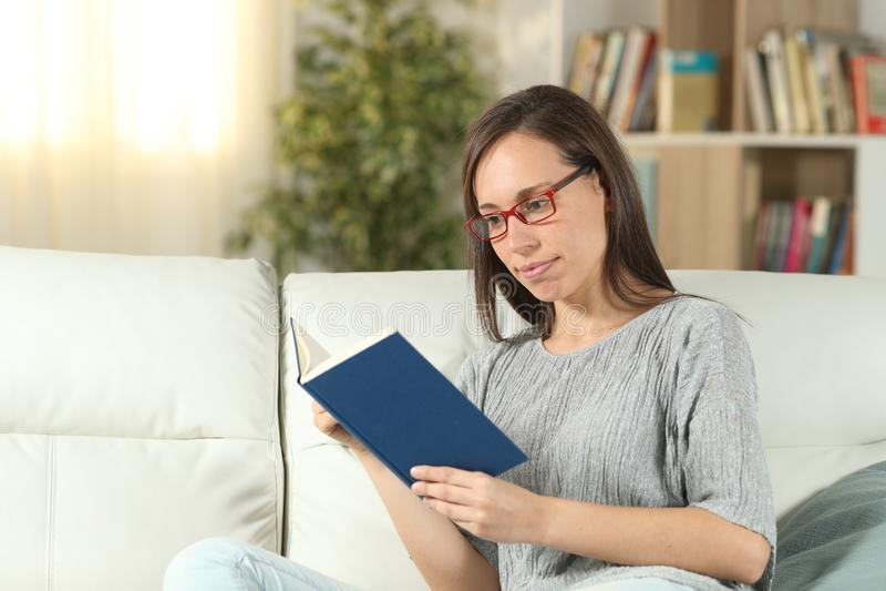 严肃的在家读书的妇女佩带的镜片 免版税库存照片