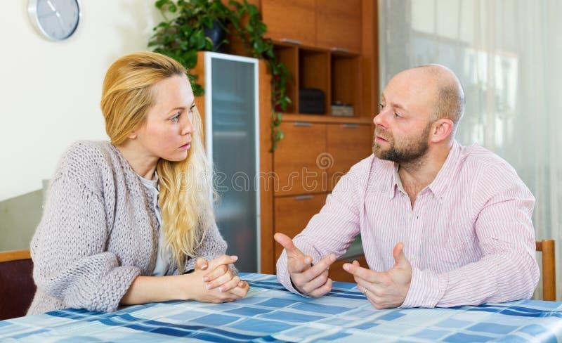 严肃的夫妇谈话在家 库存图片