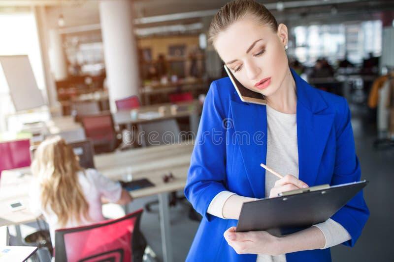 严肃的女商人在片剂写下信息 她与顾客讲话 免版税库存图片