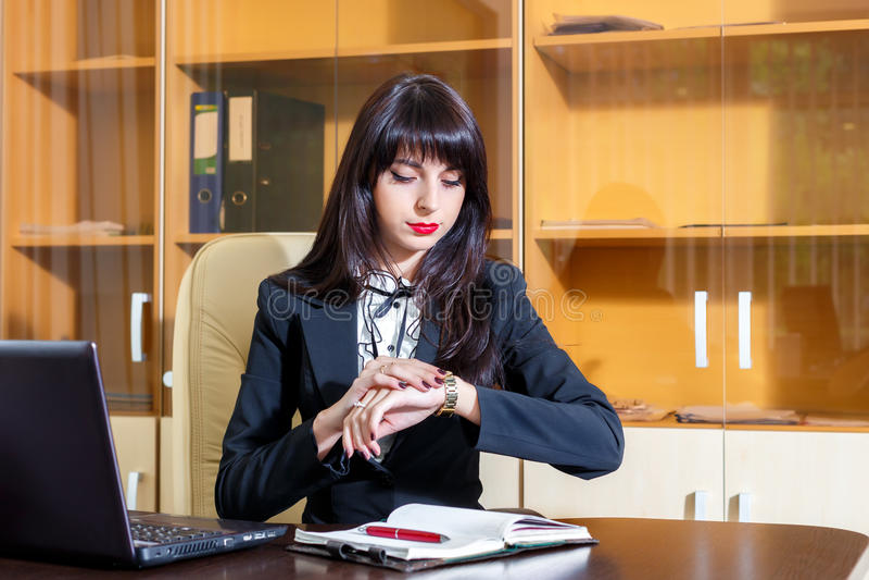 严肃的女孩在看她的手表的办公室 免版税图库摄影