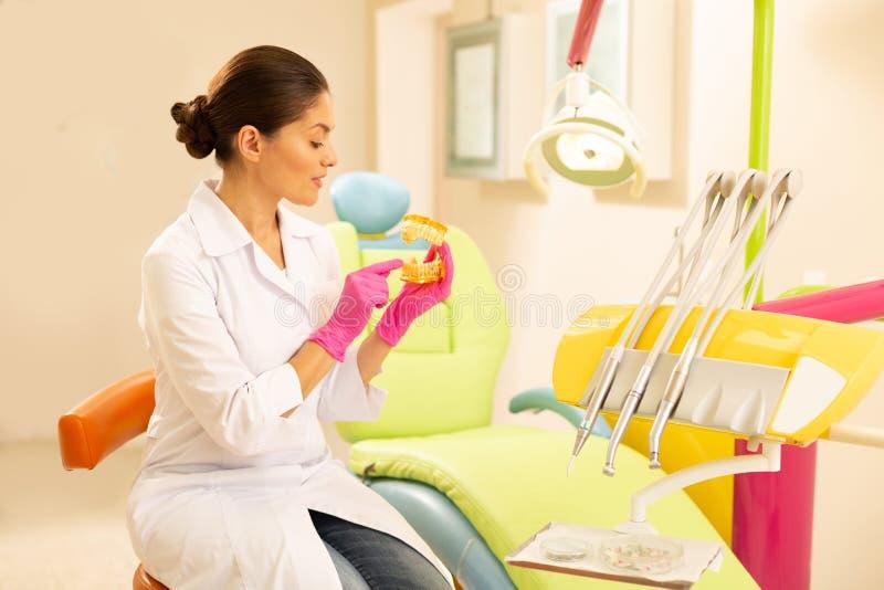 严肃的女性的牙医对负假牙塑造 图库摄影