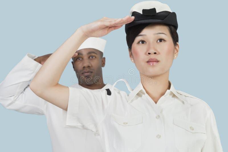 严肃的女性美国海军官员和向致敬在浅兰的背景的男性水手画象  库存图片