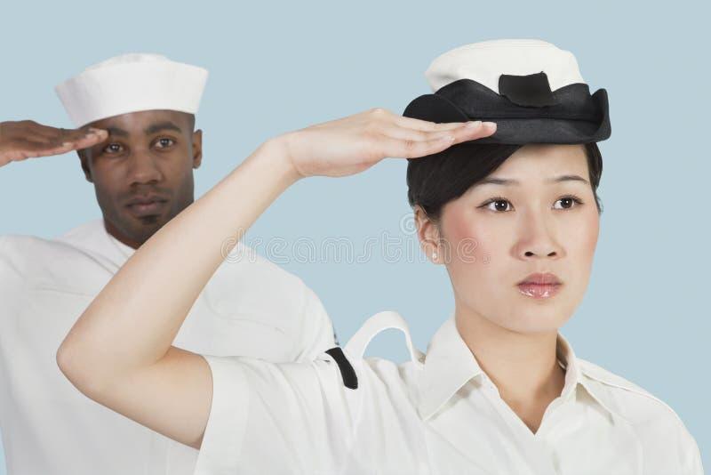 严肃的女性美国海军官员和向致敬在浅兰的背景的男性水手画象  库存照片
