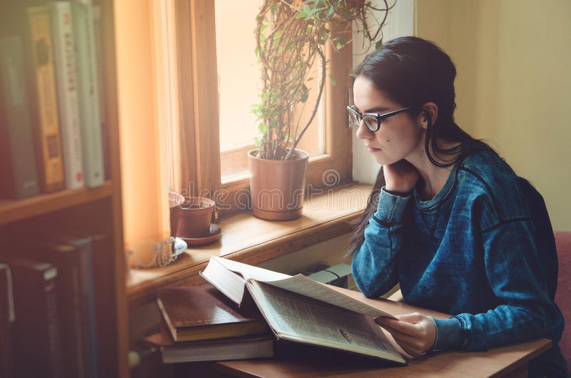 严肃的女性行家学生阅读书和开会在棕色桌上在公立大学图书馆里 年轻聪明 免版税库存照片
