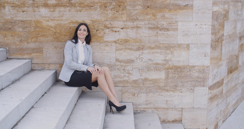 严肃的妇女坐台阶户外 免版税图库摄影