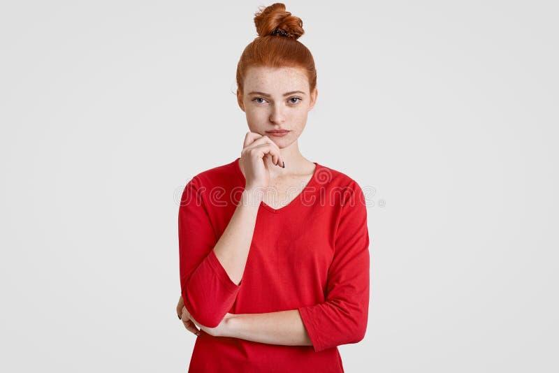 严肃的妇女照片有在小圆面包梳的红色头发的,举行下巴,保持手部分横渡,严重看照相机,认为abou 库存照片