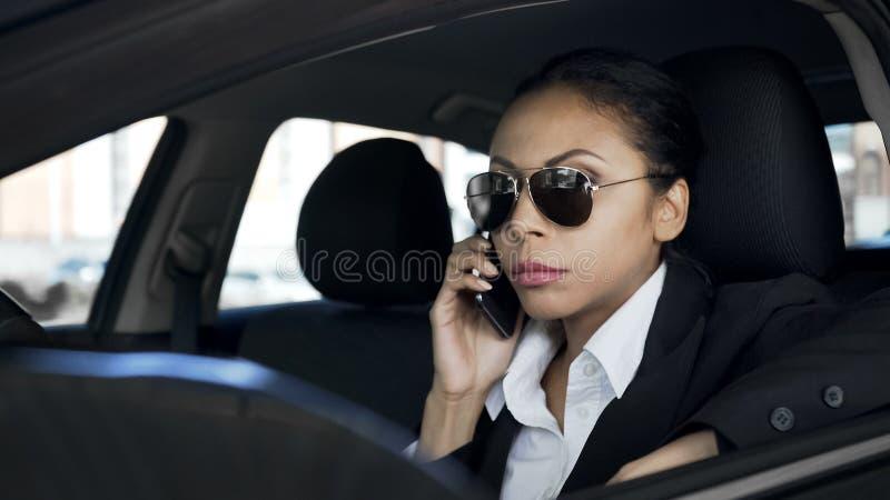 严肃的妇女谈话在汽车的电话,暗中侦察的私家侦探,警察 免版税库存图片