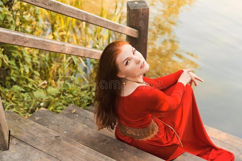 年轻严肃的妇女画象红色礼服的在河附近 免版税库存照片