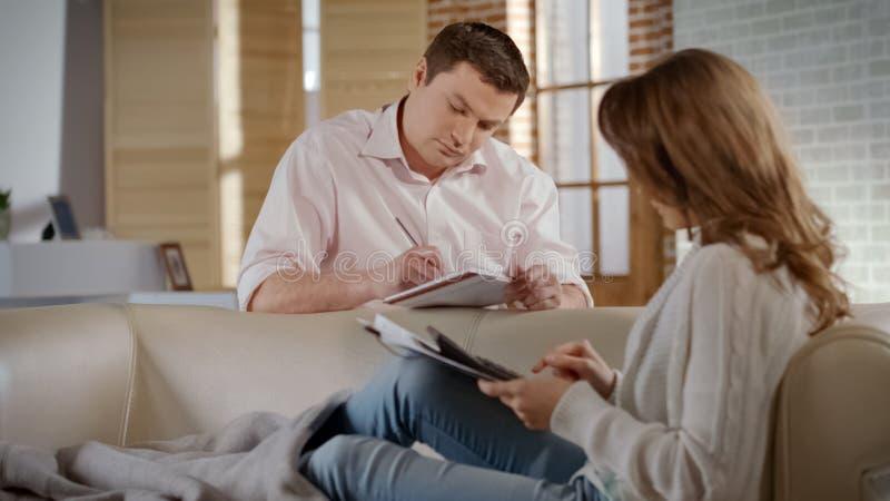 严肃的年轻夫妇计划的家庭预算,计算公共事业的费用 库存照片