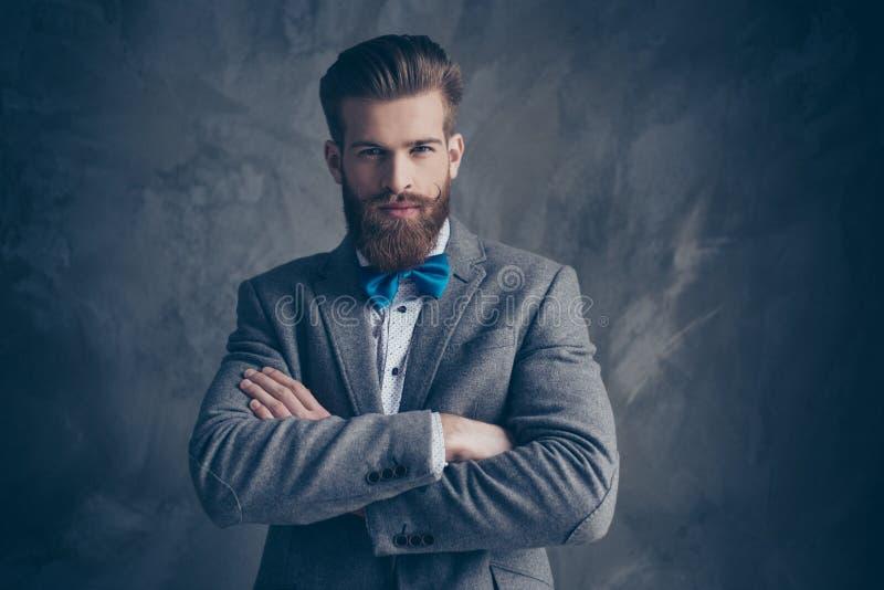 严肃的年轻有胡子的人画象有髭的在衣服st 免版税库存照片