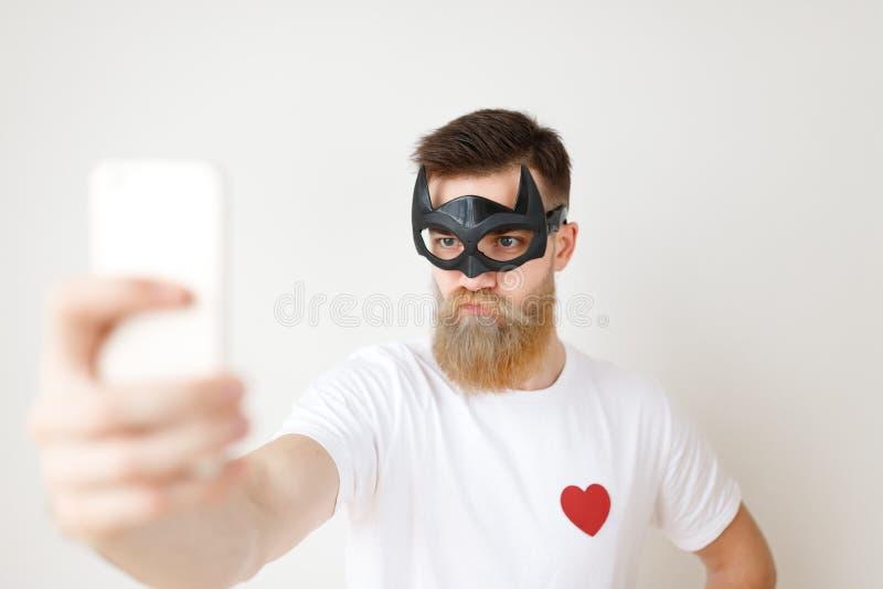 严肃的年轻男性模型水平的画象与厚实的胡子和髭的戴着马弁黑面具,偶然白色t 免版税库存照片