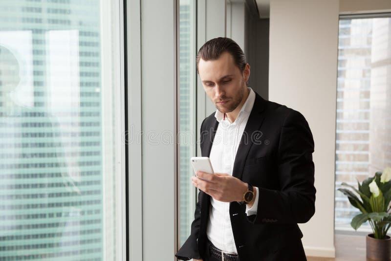 严肃的年轻英俊的商人在看c的现代办公室 库存图片