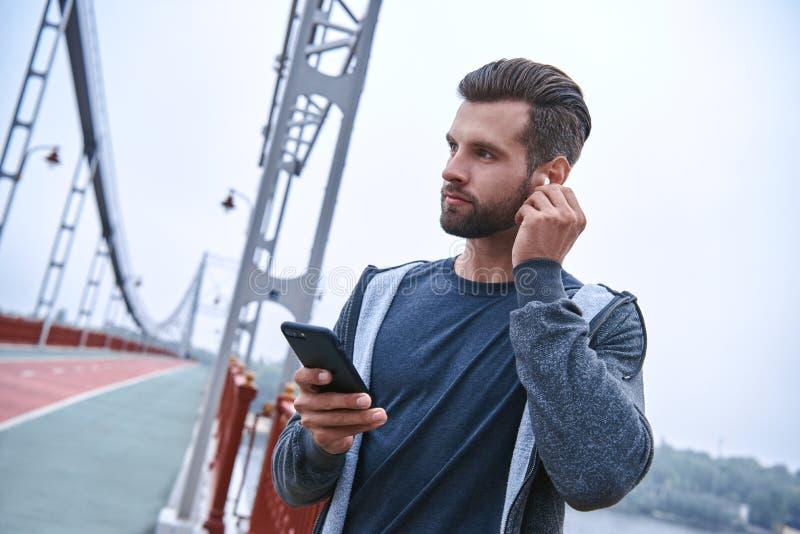 严肃的年轻运动员听的音乐和使用健身跟踪仪和智能手机户外 库存图片