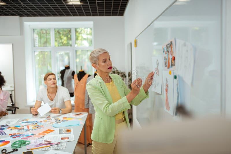 严肃的年迈的白肤金发的妇女身分在演播室 免版税图库摄影