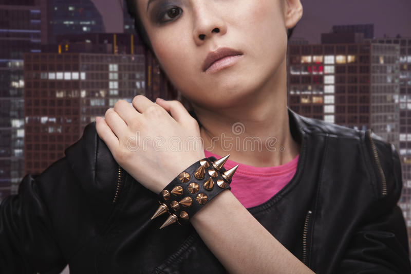 严肃的庞克摇滚乐女孩用在肩膀的手在都市风景前面 免版税库存照片