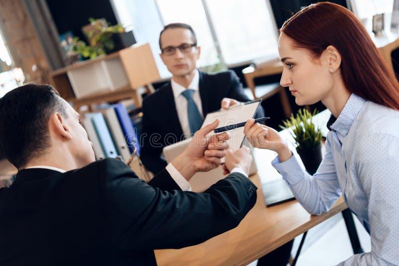 严肃的律师给成人人在离婚的标志文件 审阅离婚签署的纸的夫妇 免版税库存照片
