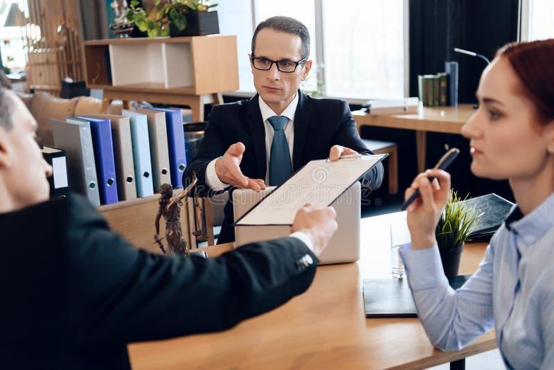 严肃的律师给成人人在离婚的标志文件 审阅离婚签署的纸的夫妇 免版税库存图片