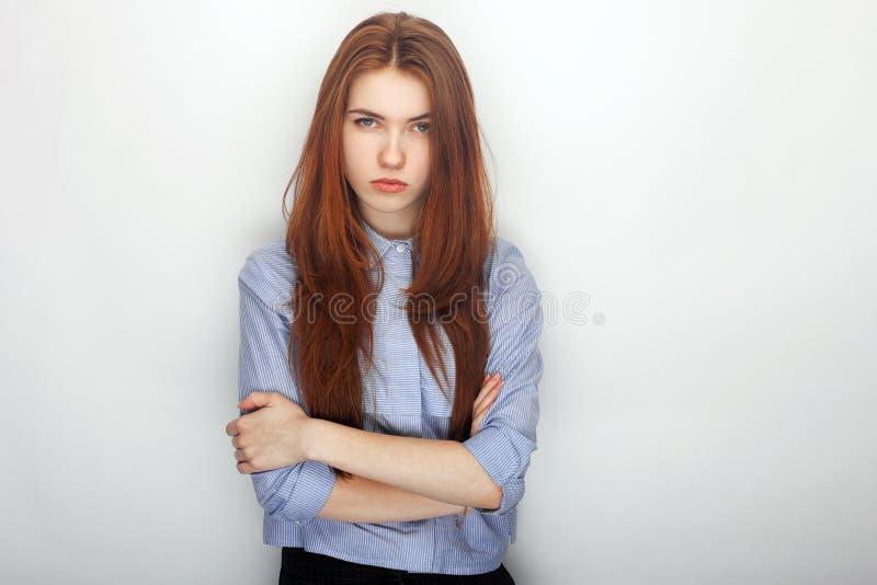 年轻严肃的恼怒的衬衣画象的红头发人美丽的妇女在拥抱的白色背景 免版税库存图片