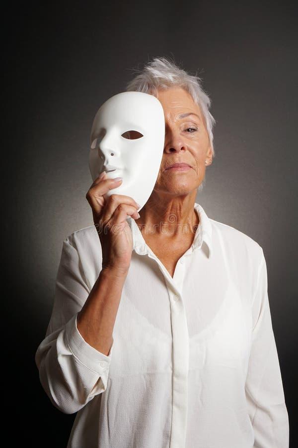 严肃的成熟在面具后的妇女显露的面孔 库存照片