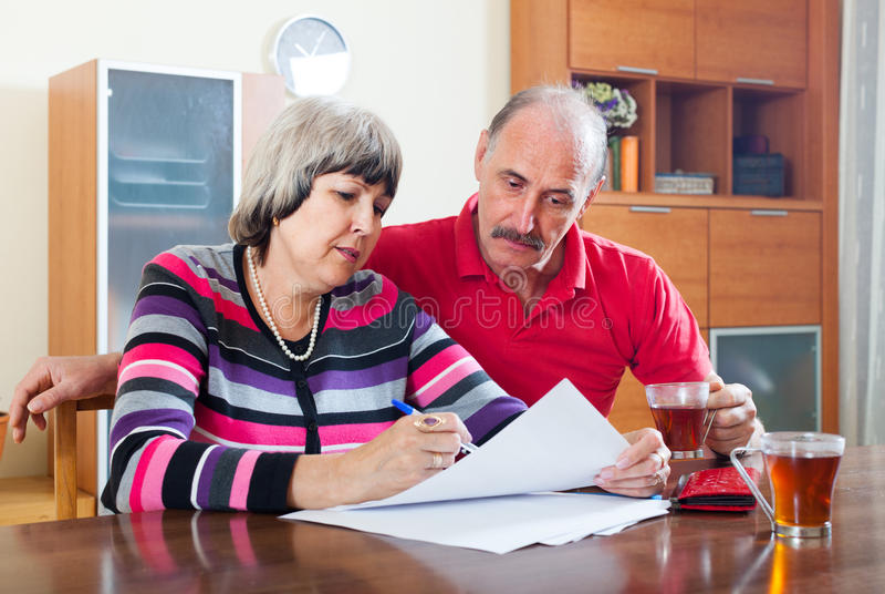严肃的成熟夫妇一起填写查询表 免版税库存照片