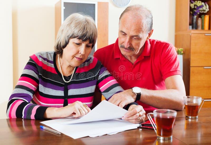 严肃的成熟夫妇读书文件 库存照片