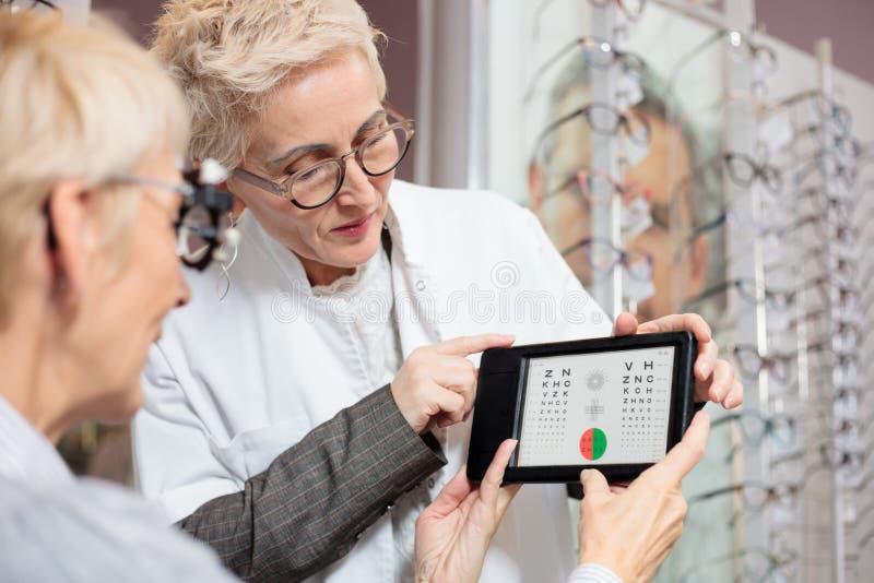 严肃的成熟女性眼科医生近视的测试的患者的视觉与测试图 免版税库存照片