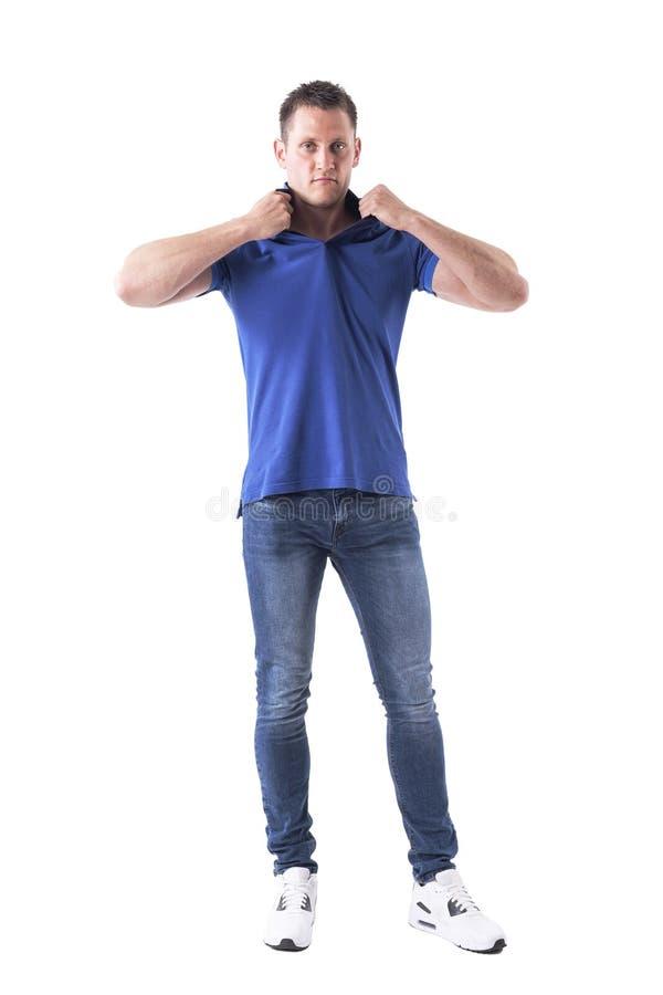 严肃的拉扯和剥去球衣衣领的态度强壮男子的男性时装模特儿看照相机 免版税库存照片