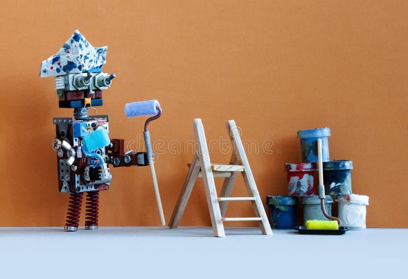 严肃的机器人画家装饰员准备好内部改善工作 木梯子、漆滚筒和桶反对 免版税库存照片