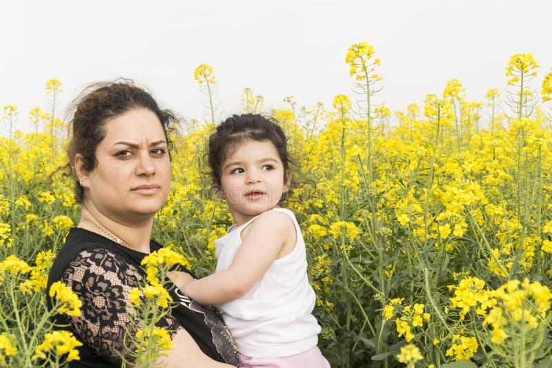严肃的母亲一起拥抱了她的女孩在油菜领域家庭获得乐趣在油菜农场 免版税库存图片