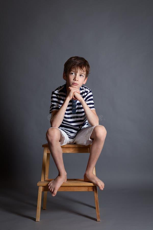 严肃的沉思哀伤的少年画象椅子的 免版税库存图片