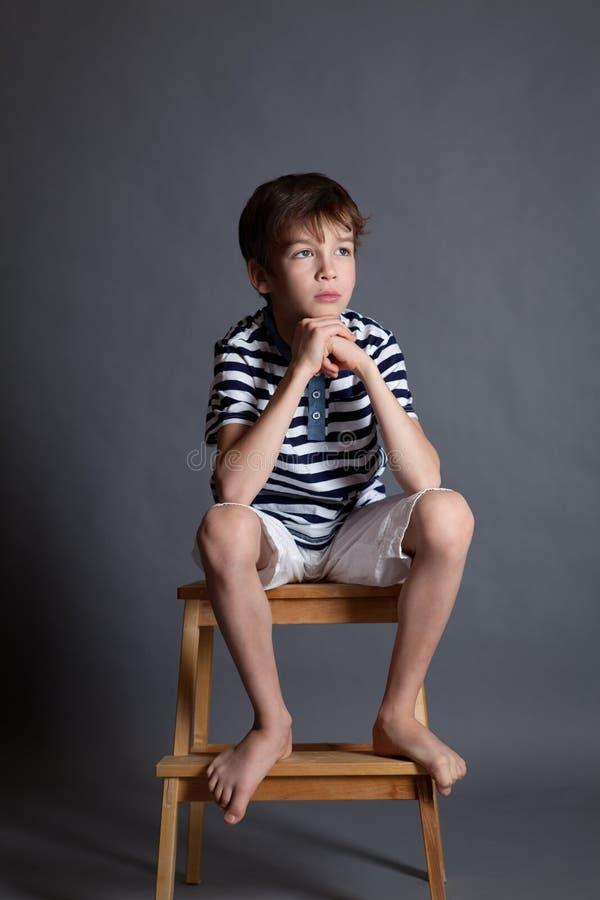 严肃的沉思哀伤的少年画象椅子的 免版税图库摄影