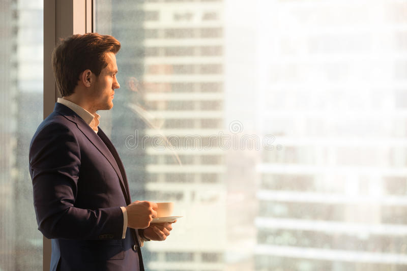 严肃的沉思商人饮用的咖啡,看日出 免版税图库摄影