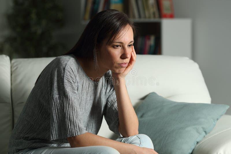 严肃的沉思妇女在家看起来去夜 免版税库存照片