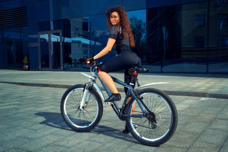 严肃的浅黑肤色的男人炫耀有自行车的妇女 库存照片