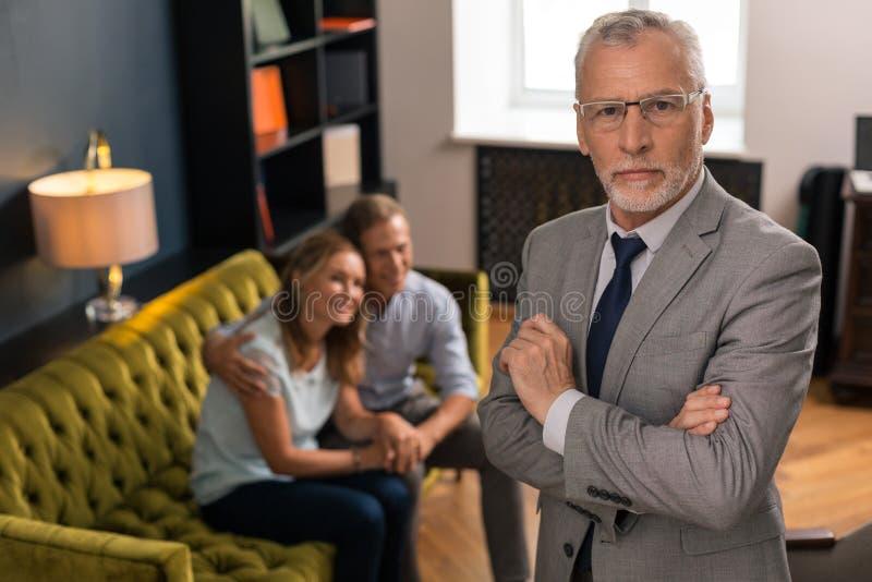 严肃的灰发的专业心理治疗家身分在他的办公室 库存照片