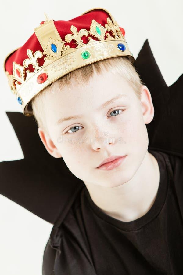 严肃的男孩佩带的冠和黑褂子 免版税图库摄影